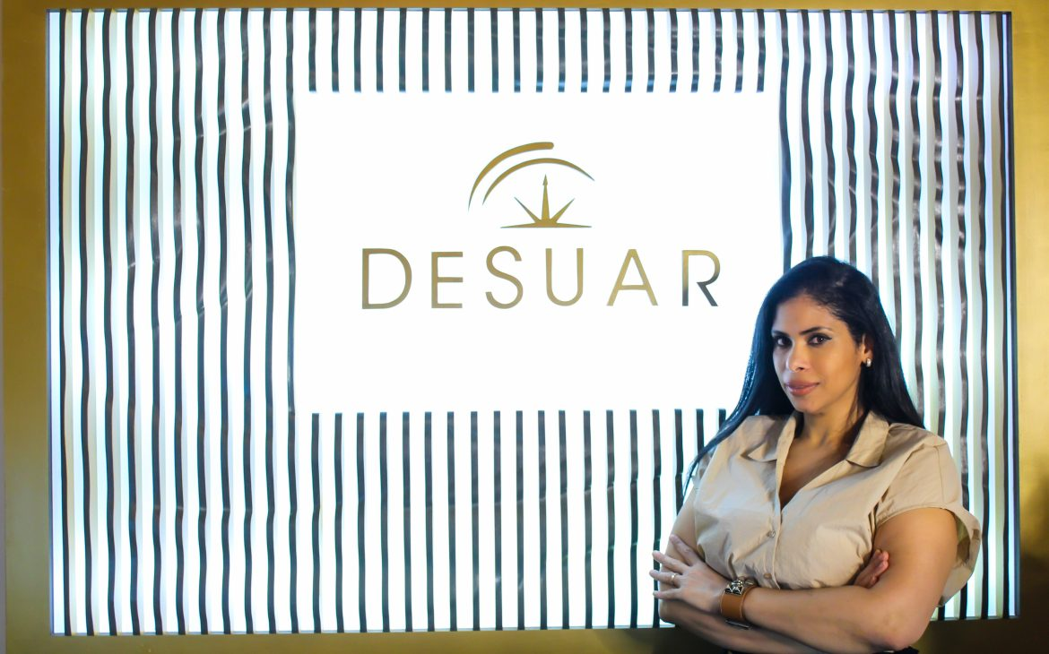 Esthetician Deisy Suarez, owner and founder of DESUAR Spa, stands in front of an illuminated DESUAR sign.