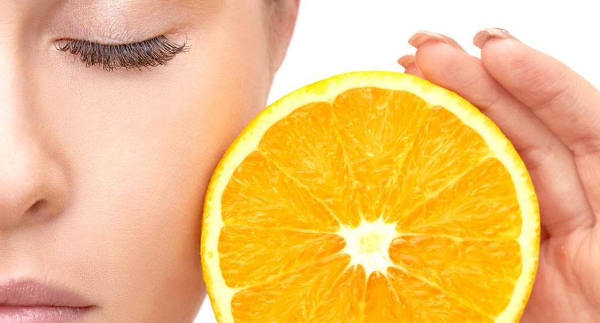 Woman holding a slice of orange next to her face