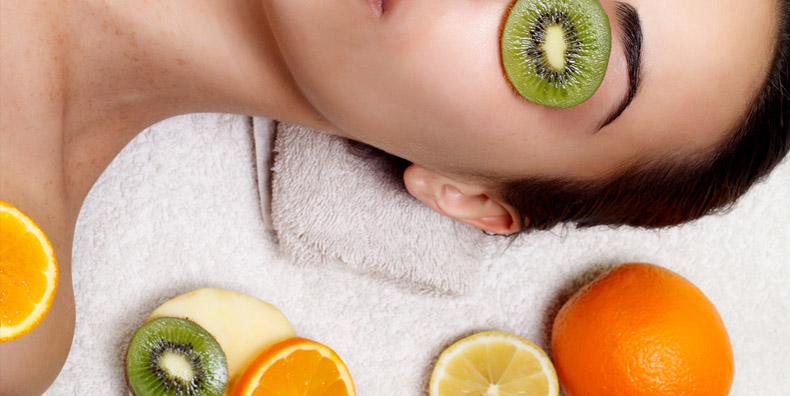 Woman surrounded by various citrus fruit