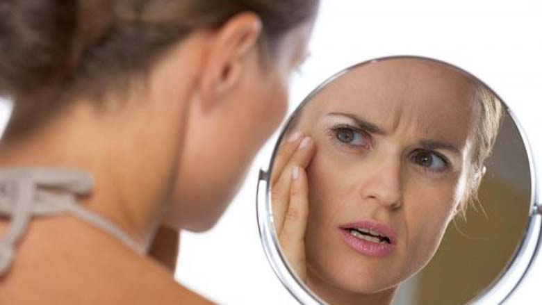 Woman examining her dull complexion in a makeup mirror
