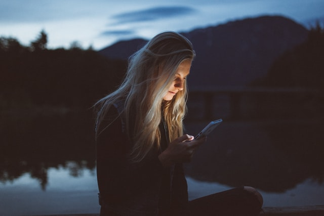 Woman by a lake in the evening, looking at her cell phone