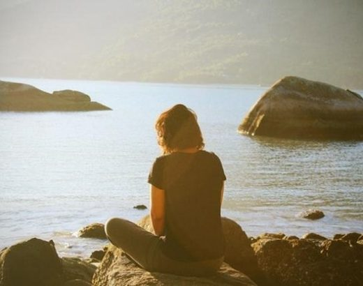 An image of a woman meditating on rocks overlooking a body of water.